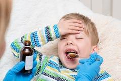 Rapaz pequeno que toma a medicina com colher foto de stock