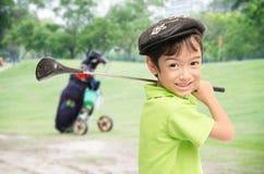 Rapaz pequeno que toma o clube de golfe no fundo branco Imagens de Stock