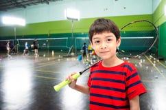 Rapaz pequeno que toma a raquete de badminton na classe de treinamento Imagem de Stock
