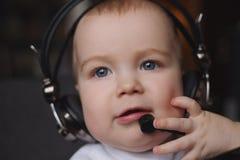 Rapaz pequeno que usa fones de ouvido com mic Fotos de Stock