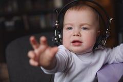 Rapaz pequeno que usa fones de ouvido com mic Fotografia de Stock