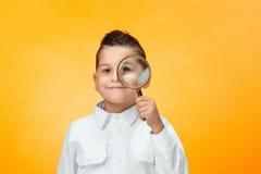Rapaz pequeno que usa a lente de aumento que olha ascendente próximo Fotografia de Stock Royalty Free