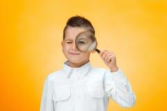 Rapaz pequeno que usa a lente de aumento que olha ascendente próximo Fotografia de Stock