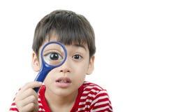 Rapaz pequeno que usa a lente de aumento que olha a planta nova Imagem de Stock