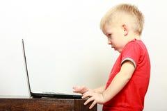 Rapaz pequeno que usa o computador do PC do portátil em casa Fotos de Stock Royalty Free