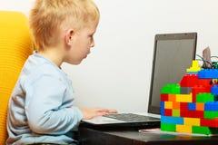 Rapaz pequeno que usa o computador do PC do portátil em casa Imagens de Stock Royalty Free