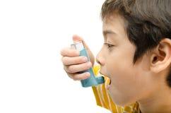 Rapaz pequeno que usa o inalador da asma para respirar foto de stock
