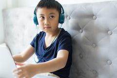 Rapaz pequeno que usa o jogo do jogo do portátil em casa para para relaxar imagens de stock