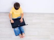 Rapaz pequeno que usa o portátil - ângulo elevado Imagens de Stock Royalty Free