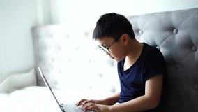 Rapaz pequeno que usa o portátil que aprende sobre a tecnologia em casa para a educação vídeos de arquivo