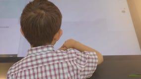 Rapaz pequeno que usa um tela táctil do suporte interativo da informação vídeos de arquivo