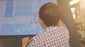 Rapaz pequeno que usa um tela táctil do suporte interativo da informação no supermercado filme