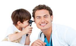 Rapaz pequeno que verific as orelhas do doutor Fotografia de Stock