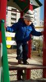 Rapaz pequeno que verifica a altura das corrediças Imagens de Stock