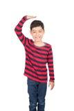 Rapaz pequeno que verifica sua altura no fundo branco fotografia de stock royalty free