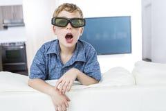 Rapaz pequeno que veste os vidros 3D e que olha a televisão Fotografia de Stock