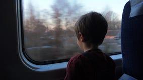 Rapaz pequeno que viaja no trem que olha fora da janela Conceito de viagem Feriados de escola adiante Assento da criança em idade filme