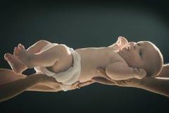 Rapaz pequeno recém-nascido com a fralda nas mãos dos pais e das mães fotos de stock royalty free