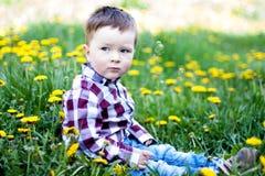 Rapaz pequeno sério bonito com flores fora Imagens de Stock Royalty Free