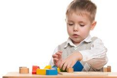 Rapaz pequeno sério na mesa Imagem de Stock Royalty Free