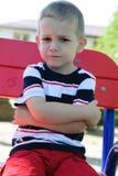 Rapaz pequeno sério que senta-se no campo de jogos Foto de Stock Royalty Free
