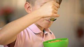 Rapaz pequeno satisfeito que come flocos de milho para o café da manhã, nutrição da infância, petisco vídeos de arquivo