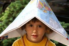 Rapaz pequeno sob o tampão do mapa de mundo Fotografia de Stock
