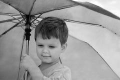 Rapaz pequeno sob um guarda-chuva. fotografia de stock