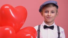 Rapaz pequeno tímido com balões coração-dados forma que sorri à câmera, presente do dia de Valentim filme