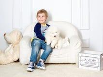 Rapaz pequeno três anos de jogo velho com cachorrinho branco Foto de Stock