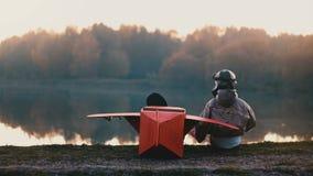 Rapaz pequeno traseiro da vista no traje piloto velho que senta-se em lago surpreendente da floresta com do plano vermelho do car vídeos de arquivo