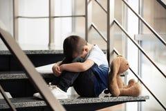 Rapaz pequeno triste com o brinquedo que senta-se em escadas foto de stock