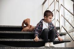 Rapaz pequeno triste com o brinquedo que senta-se em escadas fotografia de stock royalty free