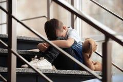 Rapaz pequeno triste com o brinquedo que senta-se em escadas imagens de stock royalty free