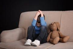 Rapaz pequeno triste com o brinquedo que senta-se no sofá imagem de stock royalty free
