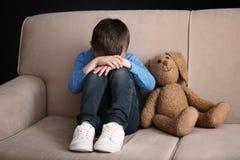 Rapaz pequeno triste com o brinquedo que senta-se no sofá foto de stock