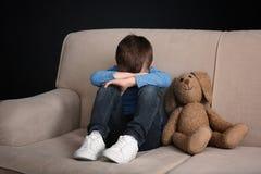 Rapaz pequeno triste com o brinquedo que senta-se no sofá imagens de stock