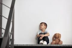 Rapaz pequeno triste com o brinquedo que senta-se perto da parede imagens de stock royalty free