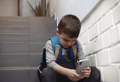 Rapaz pequeno triste com o telefone celular que senta-se em escadas imagem de stock royalty free