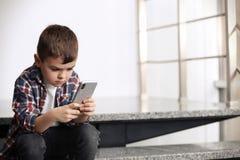Rapaz pequeno triste com o telefone celular que senta-se em escadas foto de stock royalty free