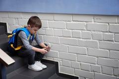 Rapaz pequeno triste com o telefone celular que senta-se em escadas imagens de stock royalty free