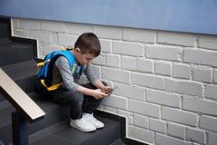 Rapaz pequeno triste com o telefone celular que senta-se em escadas fotografia de stock royalty free