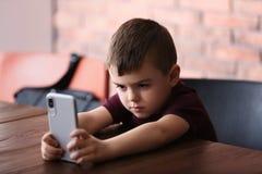 Rapaz pequeno triste com o telefone celular que senta-se na tabela imagem de stock royalty free