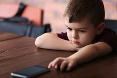 Rapaz pequeno triste com o telefone celular que senta-se na tabela foto de stock