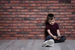Rapaz pequeno triste com o telefone celular que senta-se no assoalho Espa?o para o texto fotos de stock royalty free