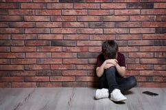 Rapaz pequeno triste com o telefone celular que senta-se no assoalho perto da parede de tijolo foto de stock