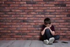 Rapaz pequeno triste com o telefone celular que senta-se no assoalho perto da parede de tijolo fotos de stock royalty free
