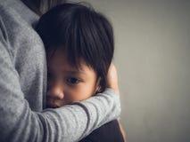 Rapaz pequeno triste do close up que está sendo abraçado por sua mãe em casa foto de stock royalty free