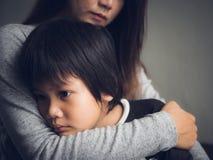 Rapaz pequeno triste do close up que está sendo abraçado por sua mãe em casa fotografia de stock