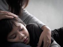 Rapaz pequeno triste do close up que está sendo abraçado por sua mãe em casa imagens de stock royalty free